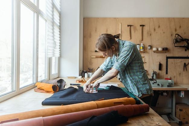 Schemat rysowania rzemieślnika podszewka do torby na tkance tworzącej wyroby kaletnicze w pracowni skórzanej w studio