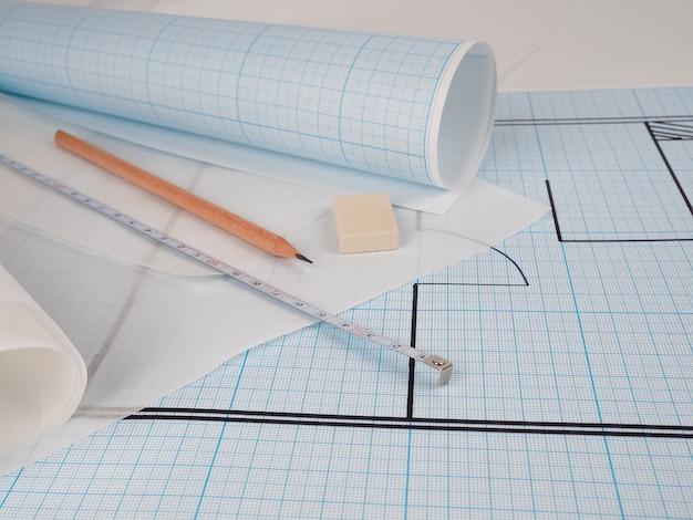 Schematyczny plan mieszkania, rysowany na papierze milimetrowym w rolce, obok pędzla konstruktor koncepcja naprawy i projektu. projekt domu, przytulna zabudowa, konstrukcja budowlana, nowa zabudowa.