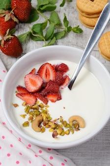 Schłodzona zupa maślankowa z jogurtu greckiego z truskawkami i pistacjami, orzechami nerkowca