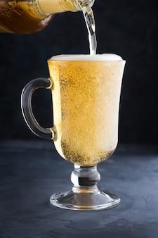 Schłodzone jasne piwo z pianką w szklanym kubku nalewanie piwa do szklanki na ladzie barowej lub pubowej