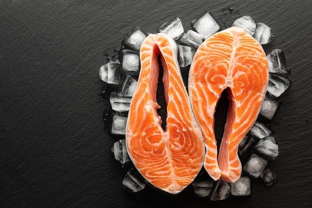 Schłodzony stek z łososia i lód na kamiennym tle, widok z góry, miejsce na tekst