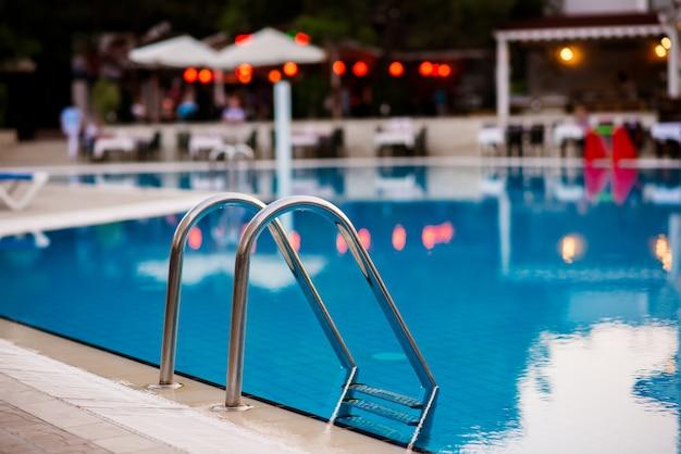 Schody do basenu na tle hotelu.