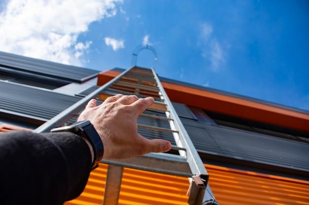 Schody do nieba. mężczyzna sięga ręką po metalowe schody w budynku na tle nieba i chmur.