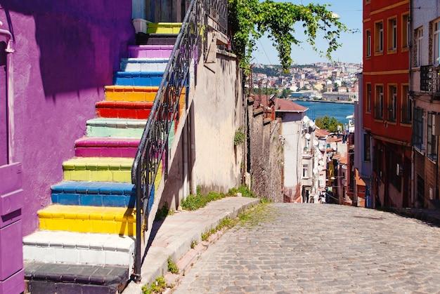Schody pomalowane na jaskrawe kolory po stronie fioletowej ściany w dzielnicy balat w stambule z otwartym widokiem na złoty róg.