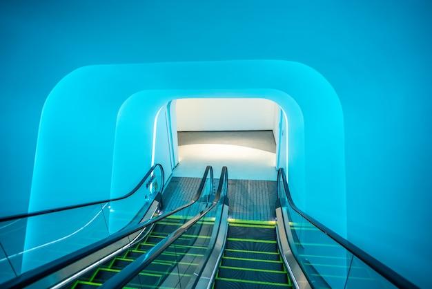 Schody ruchome w centrum handlowym pod niebieskim światłem