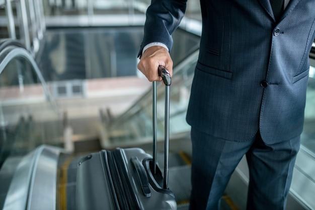 Schody ruchome w górę. mężczyzna w surowym ciemnym garniturze trzymający za rączkę walizki na schodach ruchomych w górę, bez twarzy