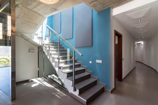 Schody we wnętrzu nowoczesnego domu betonowego, z niebieską ścianą i oprawą.