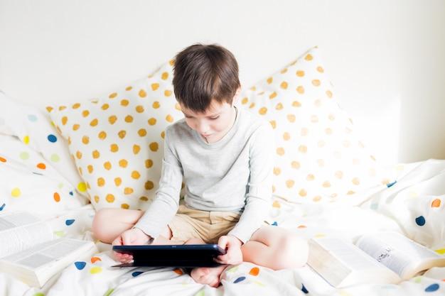 School boy na łóżku w domu z cyfrowego tabletu w ręku, odrabiania lekcji. edukacja online na odległość. kwarantanna. gra. chłopiec bawi się smartfonem