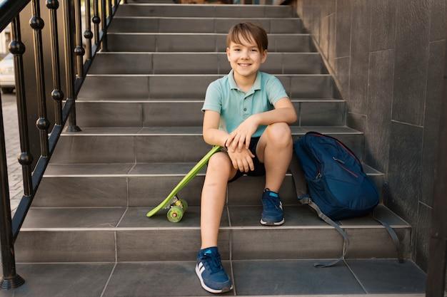School boy w niebieskiej koszulce polo siedzi na schodach z niebieskim plecakiem i zieloną tablicą