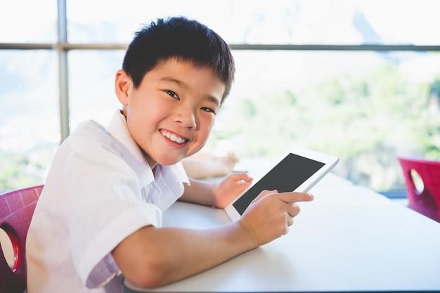 Schoolkid za pomocą cyfrowego tabletu w klasie