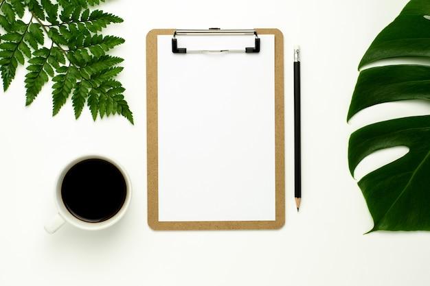 Schowek i biały papier na białym biurowego biurka tle.