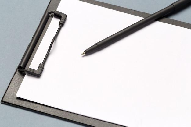 Schowek na notatki z długopisem i czystymi kartkami papieru