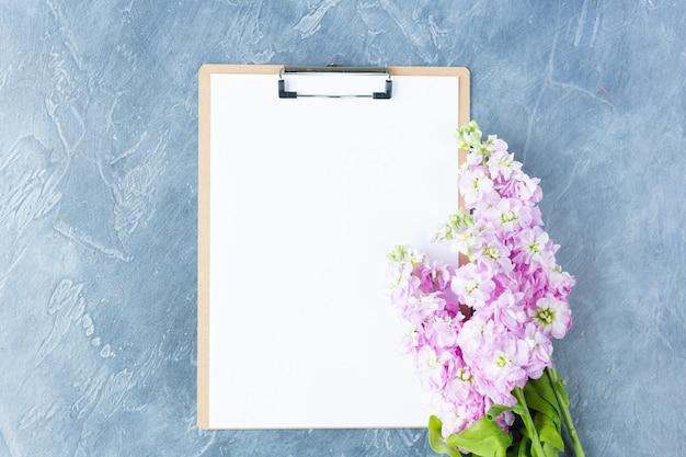 Schowek z białym czystym papierem i kwiatami na białym tle.