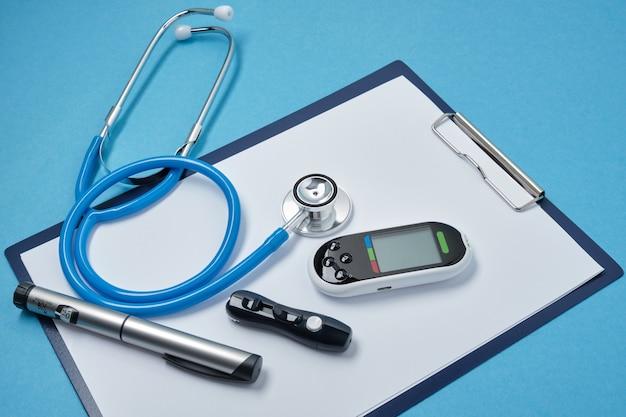 Schowek z białymi pustymi kartkami papieru, stetoskopem, glukometrem, lancetem i strzykawką z insuliną na niebieskim tle, koncepcja dnia daibetu, diagnostyka cukrzycy