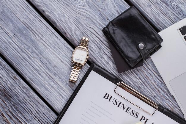 Schowek z biznesplanem i luksusowym zegarkiem. biznesmen akcesoria na białym drewnianym stole.