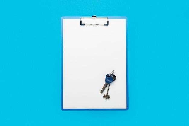 Schowek z czystą kartką i kluczami do domu lub mieszkania na niebiesko