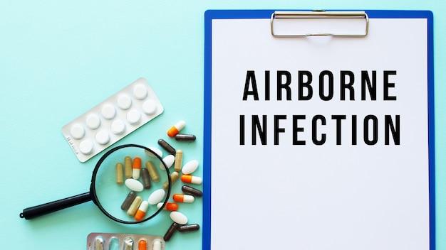 Schowek z papierem leży na stole obok narkotyków i strzykawki. napis airborne infection. pojęcie medyczne.