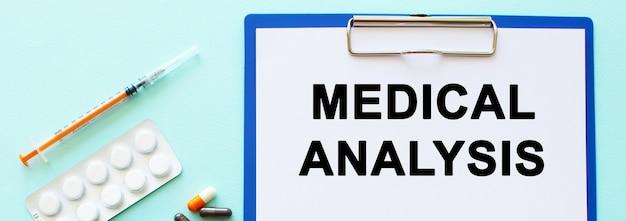 Schowek z papierem leży na stole obok narkotyków i strzykawki. napis analiza medyczna. pojęcie medyczne.