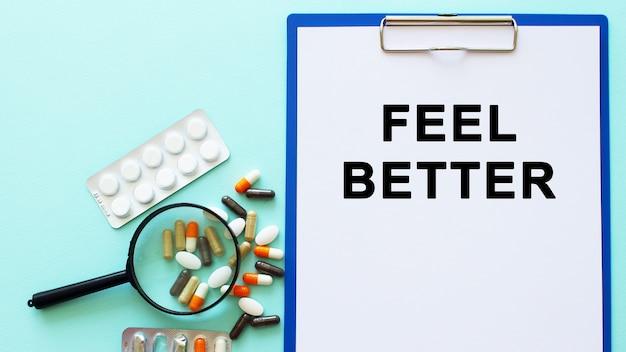 Schowek z papierem leży na stole obok narkotyków i strzykawki. napis feel better. pojęcie medyczne.