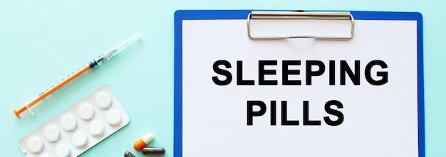 Schowek z papierem leży na stole obok narkotyków i strzykawki. napis tabletki na sen. pojęcie medyczne.