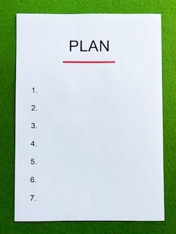 Schowek z planem tekstowym na zielonym biurku.