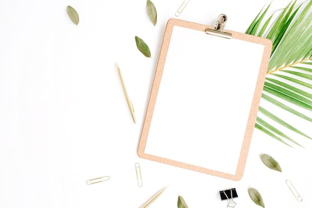 Schowek z pustą przestrzenią kopii puste, złote pióro i klipy, płatki i gałązka palmowa na białym tle.