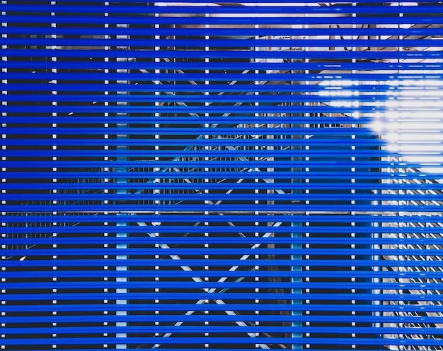 Ściana budynku przemysłowego z niebieskim metalowym wykończeniem bocznym. abstrakcyjne tło.