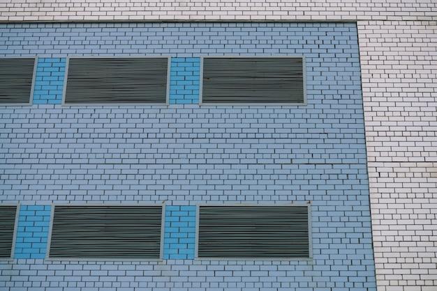 Ściana budynku spółdzielni na potrzeby sklepu, warsztatu, garażu i innych potrzeb przemysłowych. biały mur z metalowymi zamkniętymi oknami i wstawkami z niebieskiej cegły z miejsca na kopię