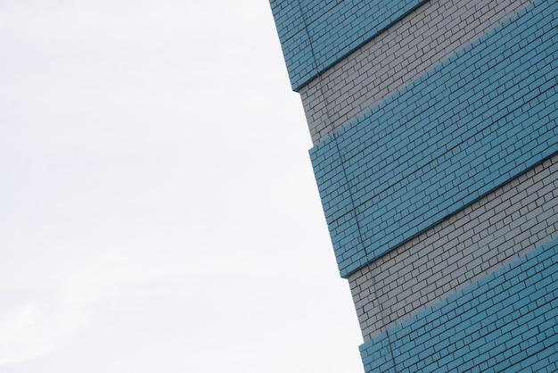 Ściana budynku spółdzielni na potrzeby sklepu, warsztatu, garażu i innych potrzeb przemysłowych. tło od białego ściana z cegieł z wstawieniami błękitny ceglany zakończenie z kopii przestrzenią na niebie. przekątna.
