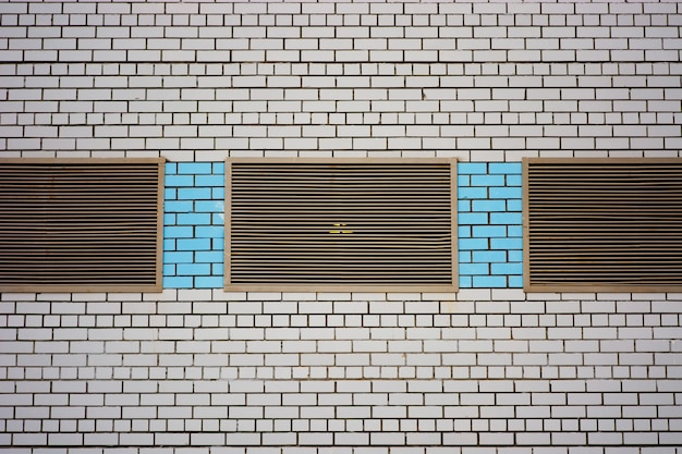 Ściana budynku spółdzielni na potrzeby sklepu, warsztatu, garażu i innych potrzeb przemysłowych. tło z białym murem z metalowymi zamkniętymi oknami i wstawkami z niebieskiej cegły z bliska.