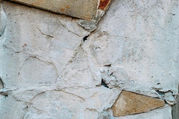 Ściana cementowa z ubytkami i śladami płytek. tło i miejsce na tekst.