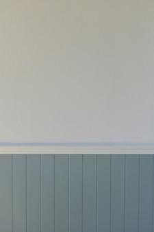 Ściana domu w stylu vintage ma białą ścianę z fakturą, a dolną część stanowi niebiesko-szara listwa.