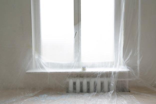 Ściana i okno zabezpieczone folią z tworzywa sztucznego we wnętrzu remontowym domu