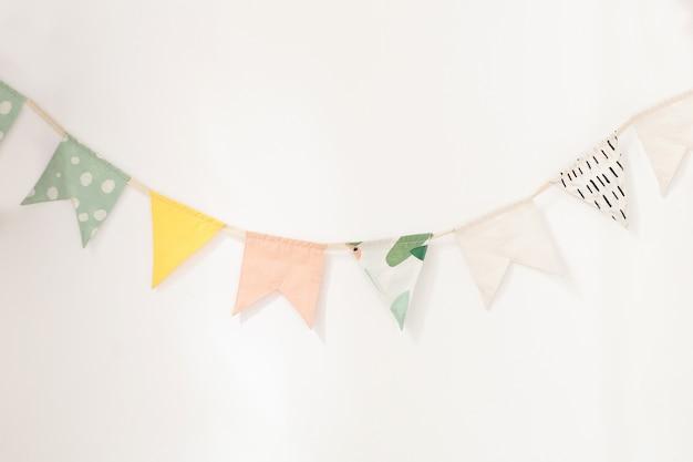 Ściana ozdobiona jest wielobarwnymi flagami dla dzieci. flagi dekoracyjne dekoracje urodzinowe.