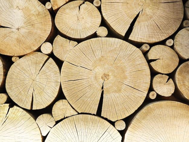Ściana ozdobiona ułożonymi drewnianymi balami. wytnij pnie drzew teksturowane tło