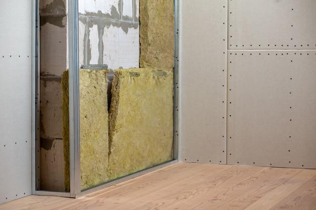Ściana remontowanego pomieszczenia z izolacją z wełny mineralnej i metalową ramą przygotowaną na płyty gipsowo-kartonowe.