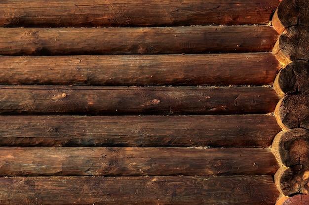 Ściana rosyjskiego krajowego domu drewnianego. domek z bali lub stodoła niepomalowane okorowane ściany teksturowane poziome tło z miejsca na kopię.