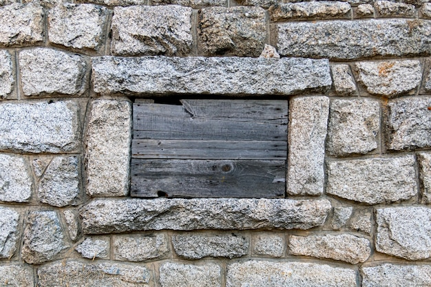 Ściana skalna i zamknięte okno pokryte drewnianymi paletami okna z desek