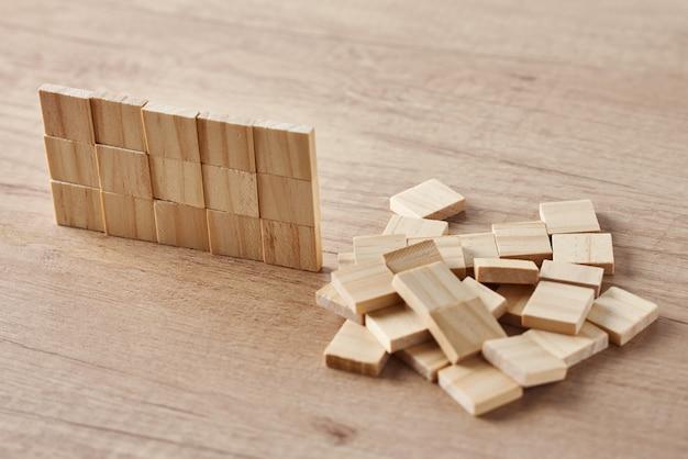 Ściana wykonana z drewnianych klocków na stole z drewna. koncepcja zadania końcowego
