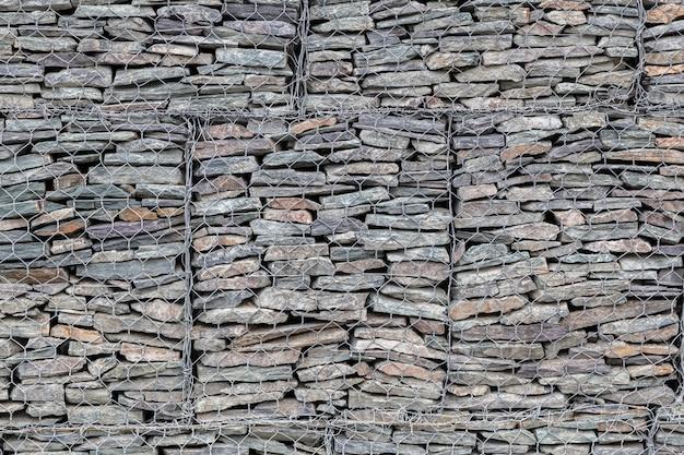 Ściana wyłożona małymi szarymi kamieniami za metalową kratą