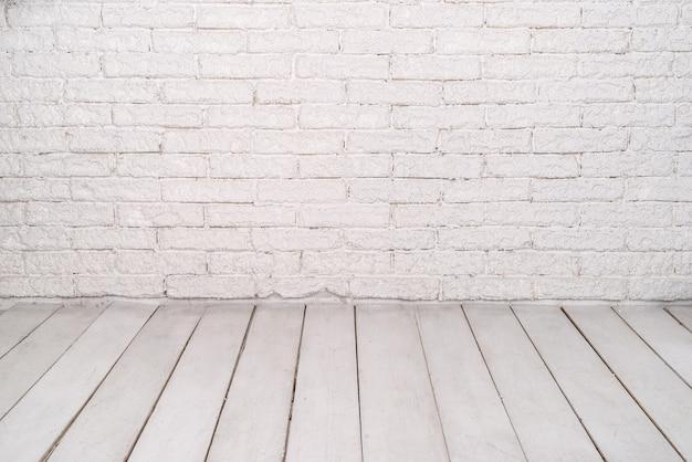 Ściana z białej cegły i kamienia oraz jasna drewniana podłoga