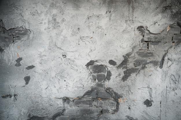 Ściana z cegły jasnoszarej z odpadającym tynkiem. stare sztukaterie w murze. streszczenie tło lub tekstura.