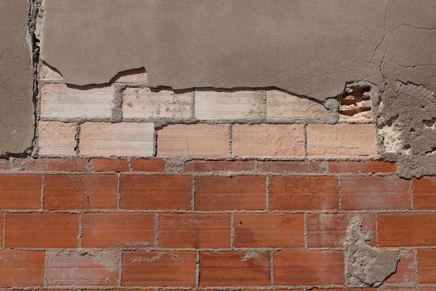 Ściana z czerwonej cegły pod teksturą uszkodzonego tynku z popękanym szarym betonem