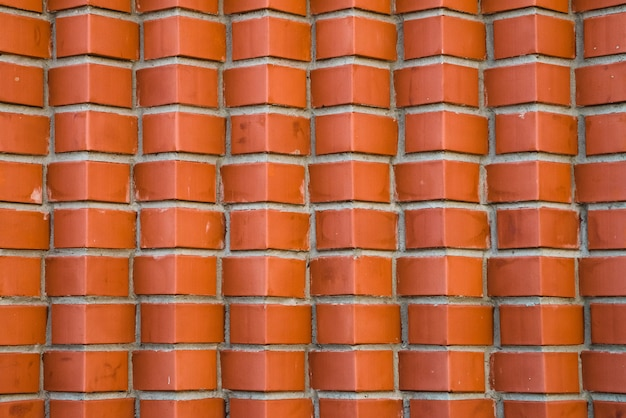 Ściana z czerwonej cegły z cegieł ukośnych. geometryczny obraz tła z cegły brązowy róg.