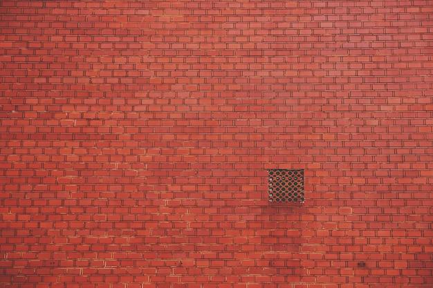 Ściana z czerwonej cegły z kwadratowym otworem wentylacyjnym