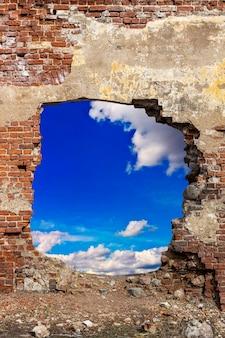 Ściana z czerwonej cegły z otworem z błękitnym niebem i chmurami. zdjęcie wysokiej jakości