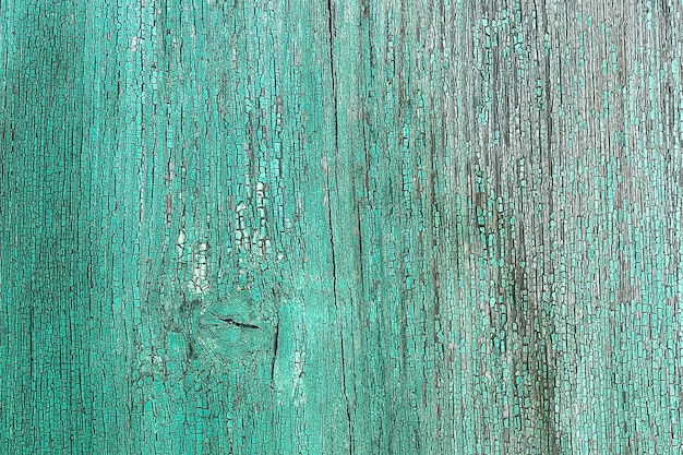 Ściana z drewnianych desek koloru niebieskiego z pęknięciami. tło dla projektu.