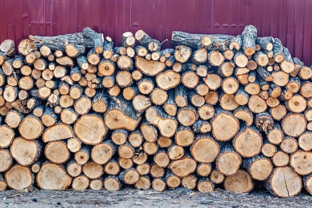 Ściana z ułożonego drewna opałowego zebranego na sezon zimowy do ogrzewania domu lub łaźni i sauny