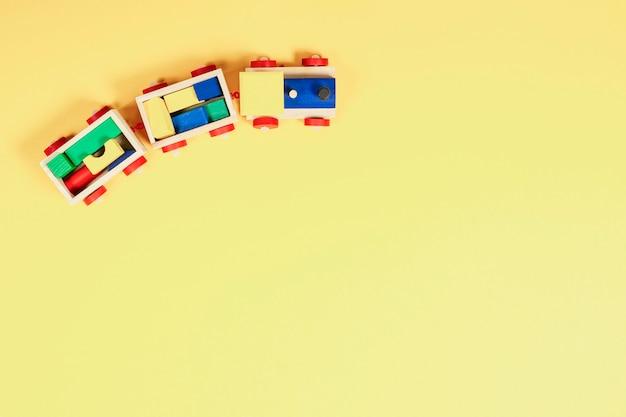 Ściana z zabawkami dla dzieci. widok z góry na drewniany pociąg zabawkowy z kolorowymi klockami na żółtej ścianie.