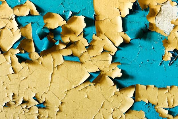 Ściana z żółtą i niebieską farbą w pęknięciach. zdjęcie wysokiej jakości